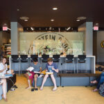 Students sit in cafe common area on campus.