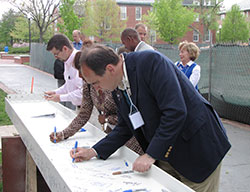 Board of trustees member David Otfinoski signs a steel beam to be used in the construction of the Johnson Center.