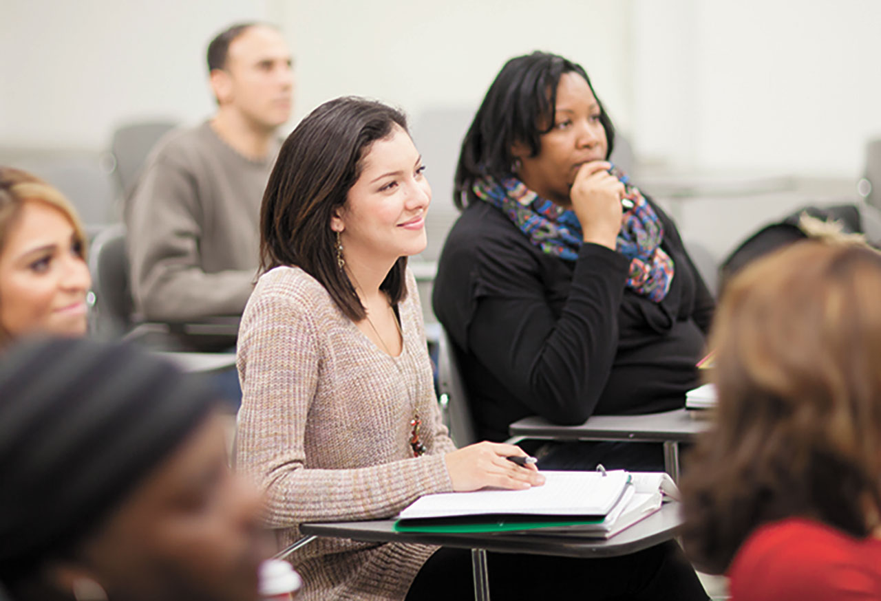 Adult students sit in the classroom attentive to the professor.