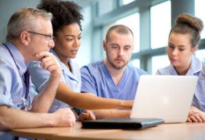 Nursing students crowd around a laptop.