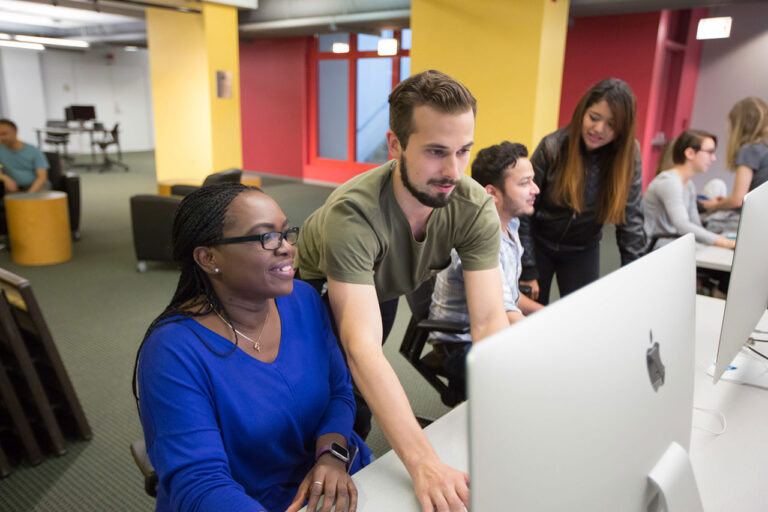 Several students gathered in brightly colored computer lab. Male student directs computer mouse while female student watches monitor.