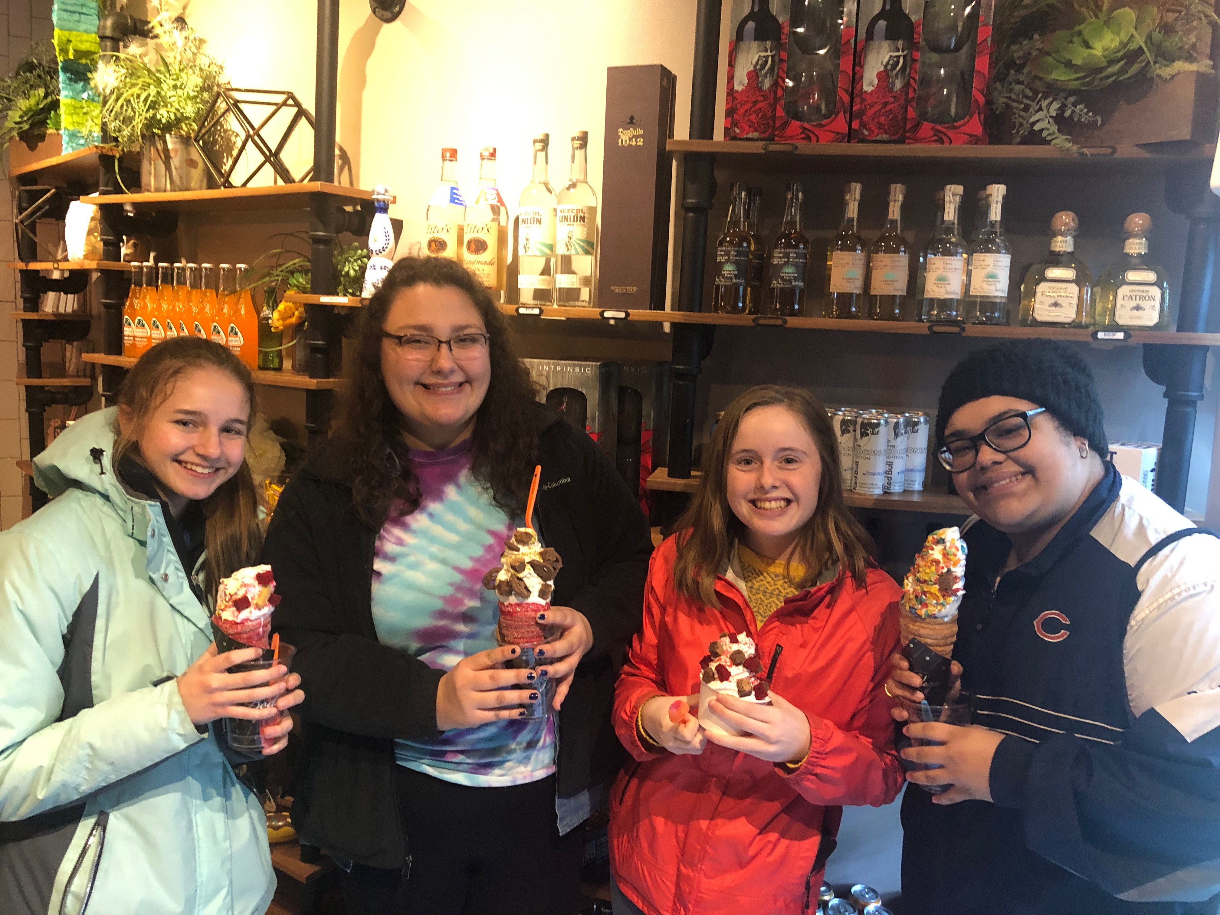 Four young women holding ice cream desserts in a small shop.