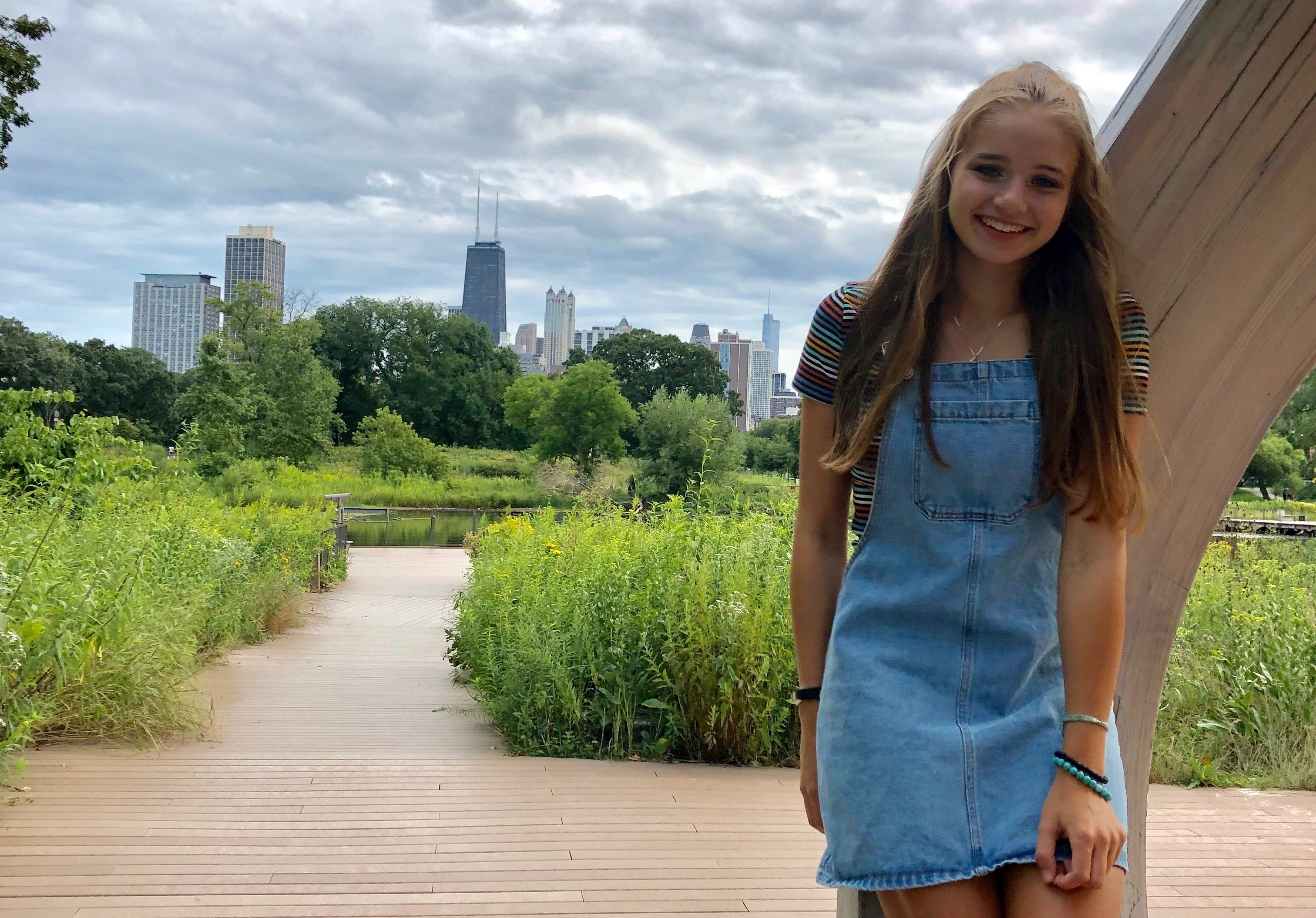A young woman standing on a park pathway with the Chicago skyline behind her.