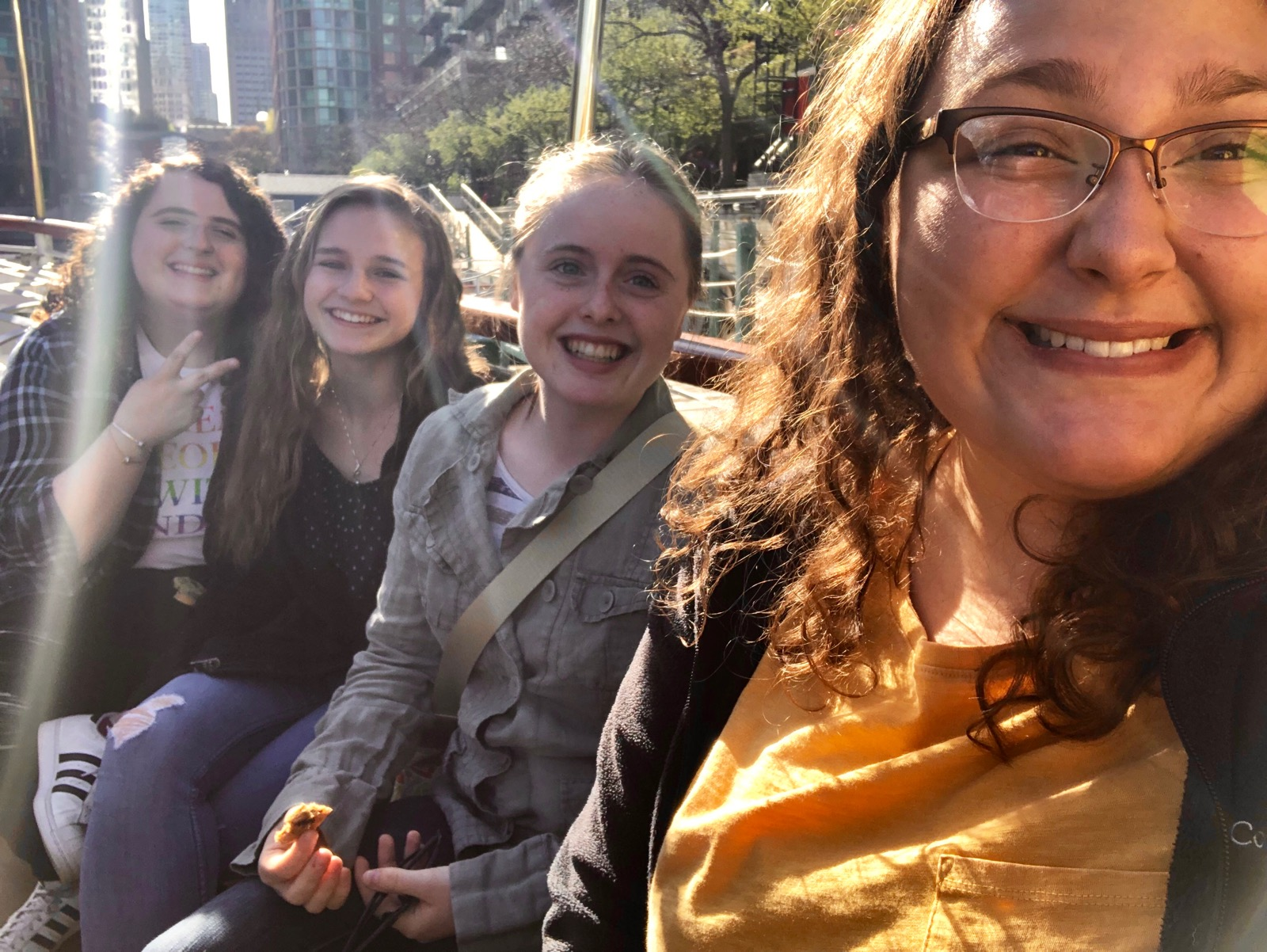 Four young women smiling while riding a water taxi, downtown Chicago