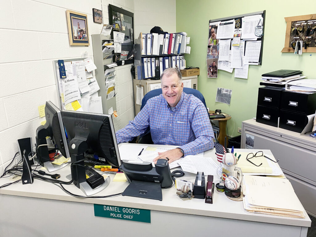 Man smiles from behind his desk.