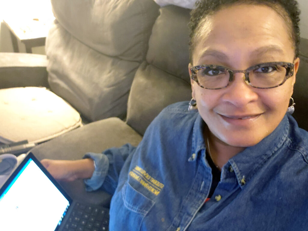 Andrea Nevels sits on a beige sectional with her laptop.