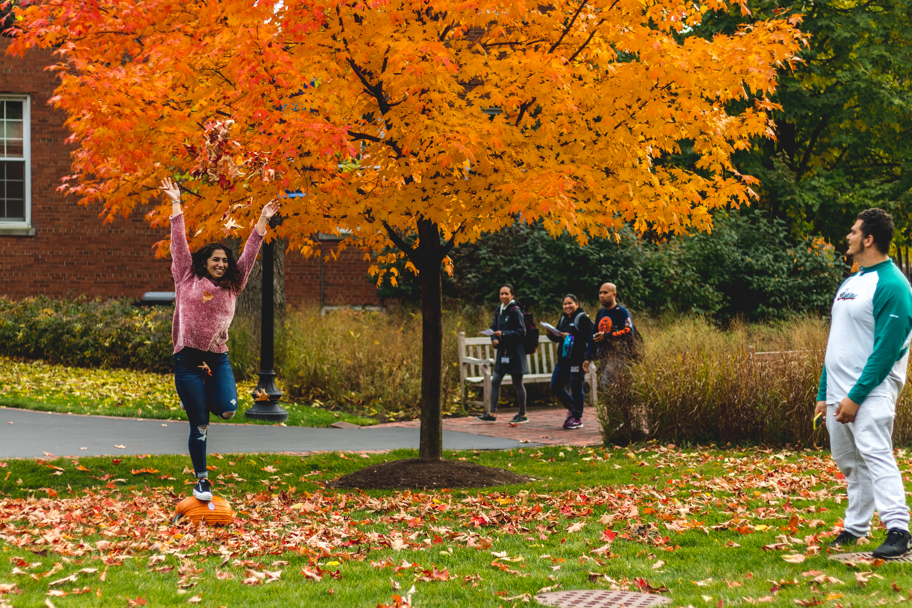 Female student balances on a pumpkin under tree with bright orange leaves. Other students stroll across the greenspace. Campus reopens for the fall 2020 semester, following closure due to COVID-19 concerns.