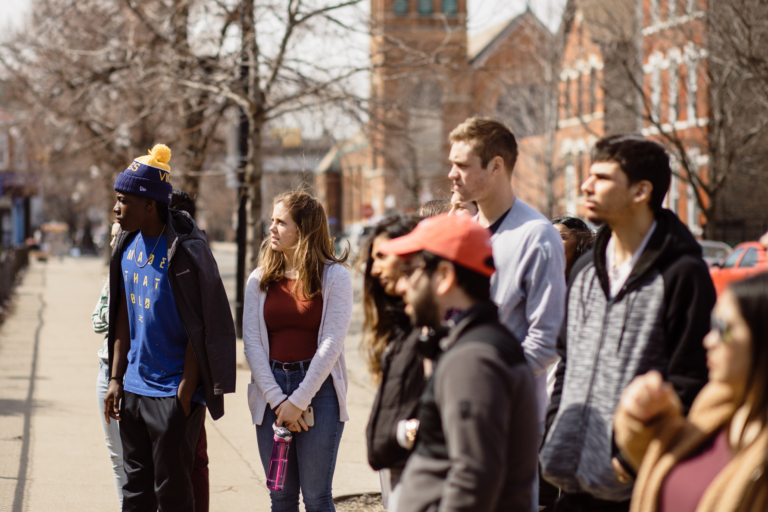 Students stand on city sidewalk examining Chicago architecture.