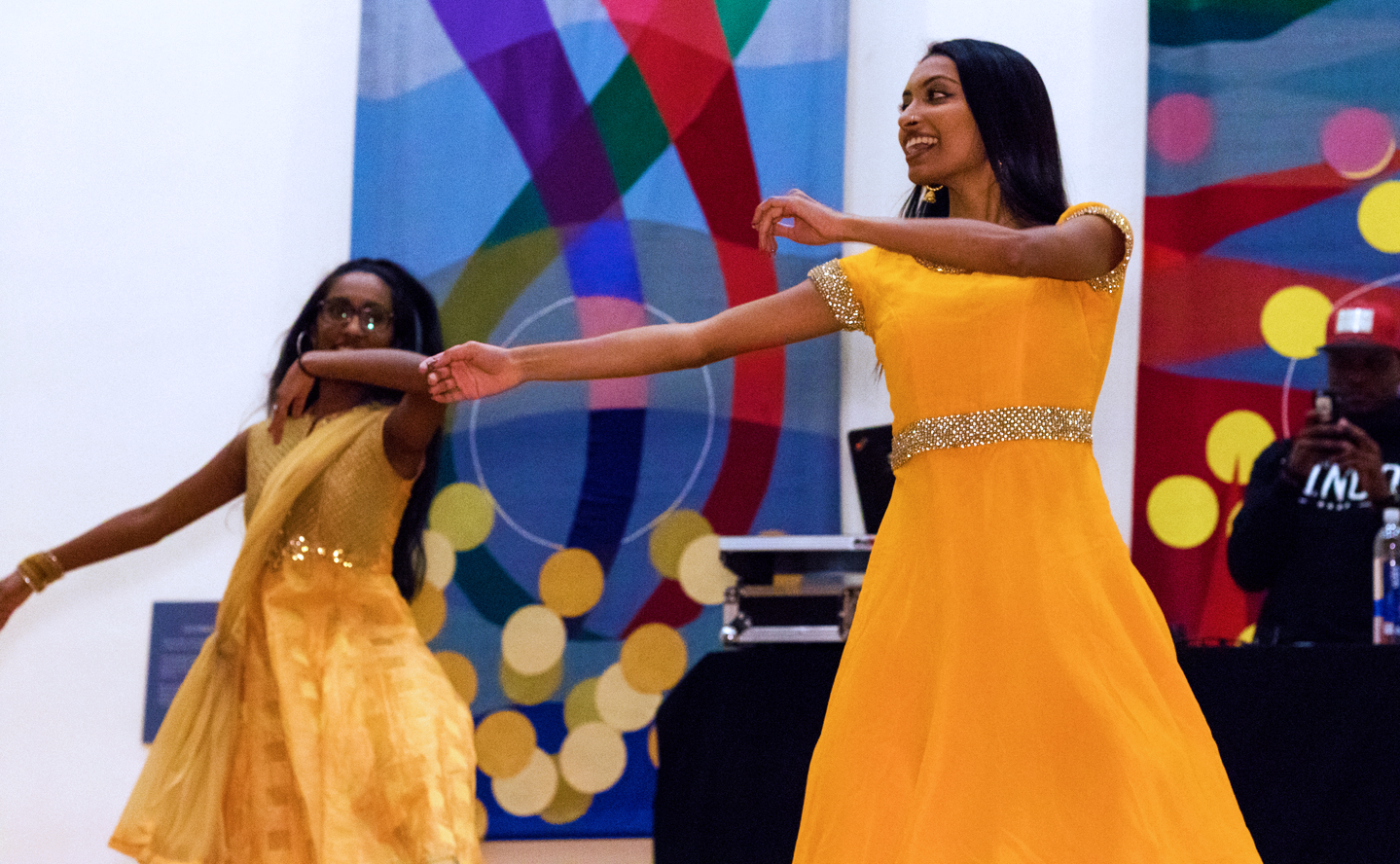 Two women in yellow dresses perform traditional dances at Diwali Festival.