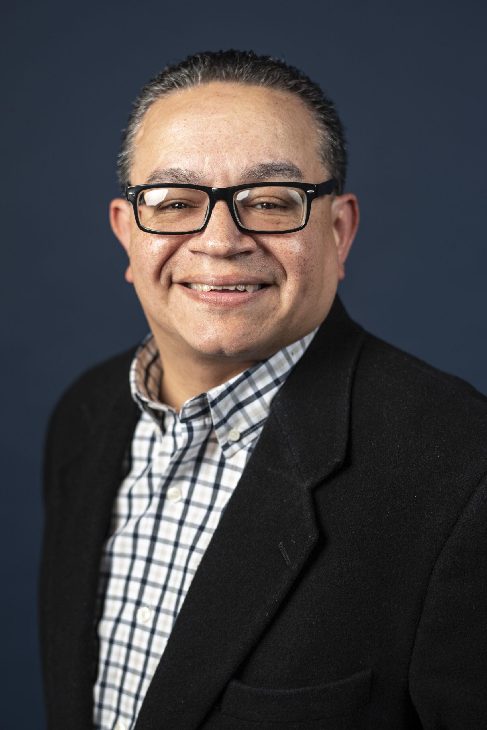 man in black glasses, blue plaid dress shirt and black jacket
