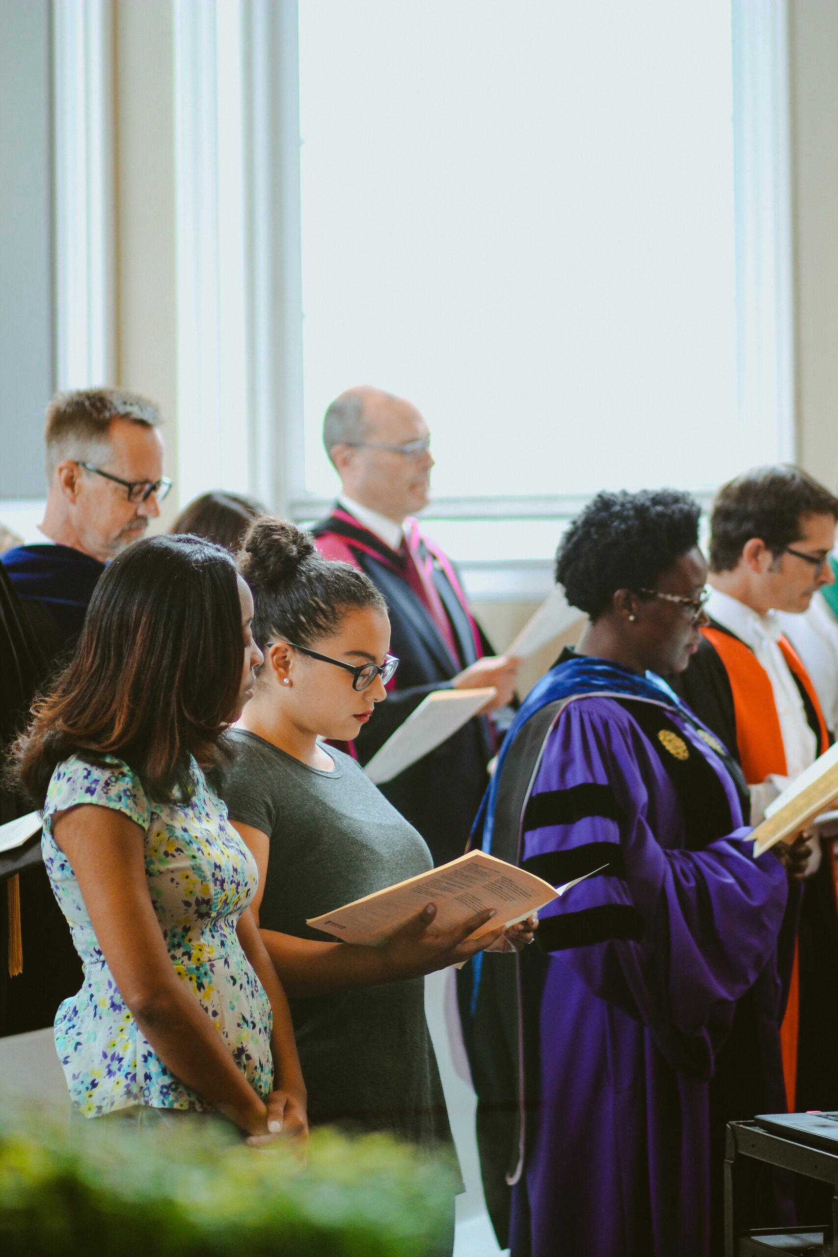 Congregation sings in chapel pews.