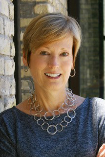 Smiling woman wearing blue top and silver hoop necklace