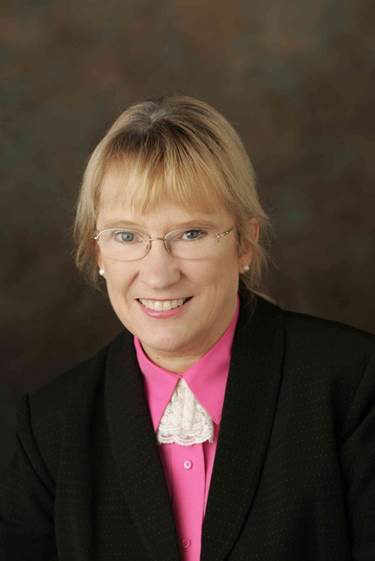 Smiling woman in black suit, pink collar, and glasses