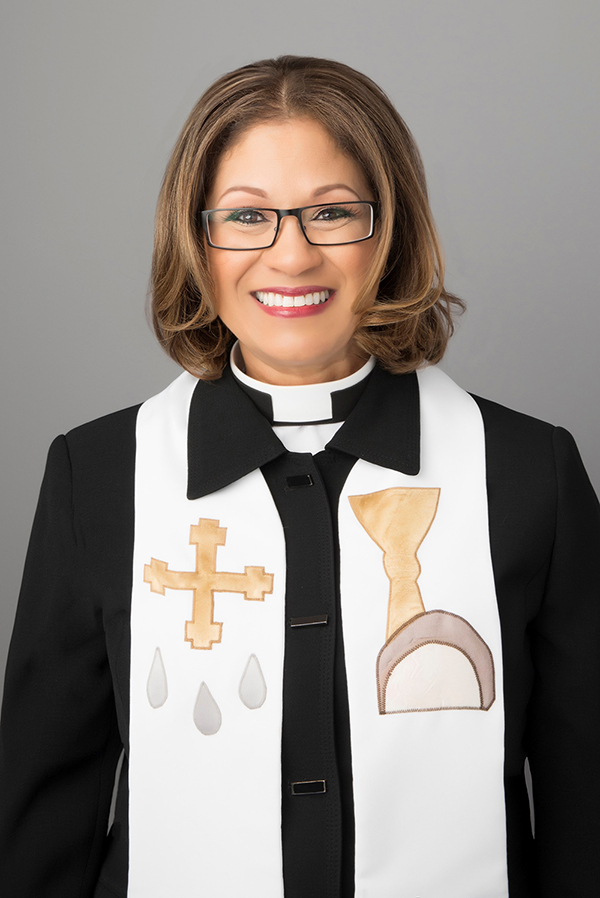 Smiling woman wearing clergy robe and shoal