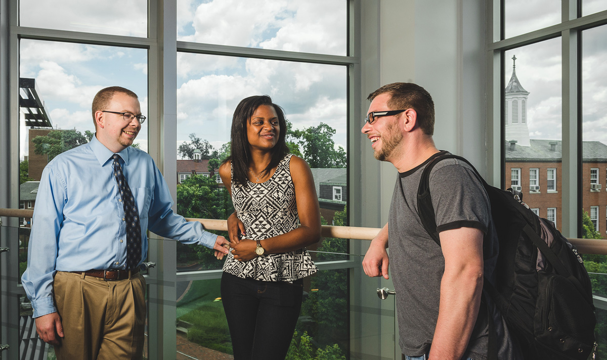 Professor and two students stand chatting in front of full length windows overlooking campus.