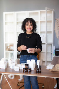 Woman stands in sunlit workspace behind a table spread with personal care products.