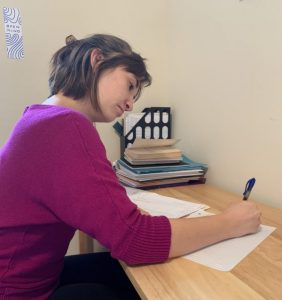 A North Park University Writing Center Writing Advisor (peer tutor) sits at a desk, composing a letter to her Letter Partner, an incarcerated student at the North Park Stateville Correctional Center Campus.